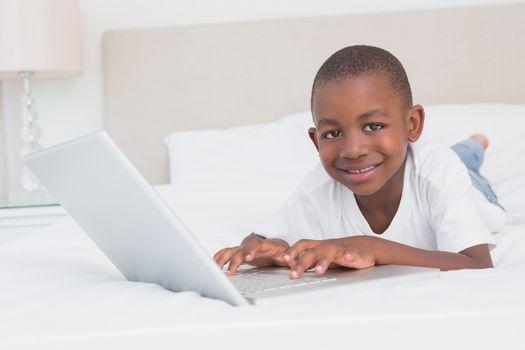 Portrait of a pretty little boy using laptop in bed