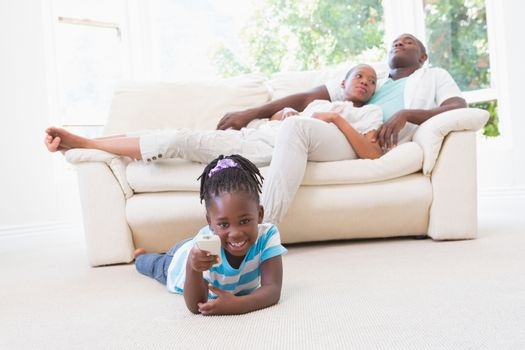 Pretty couple sitting on couch and their daughter playing