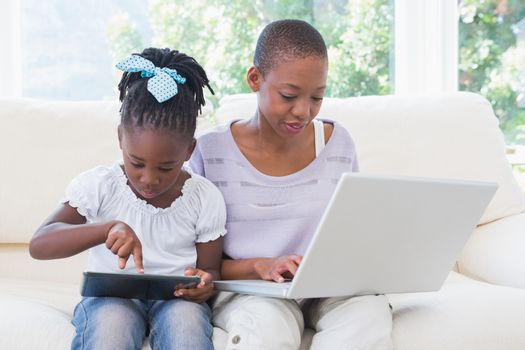 Happy smiling mother using laptop with her daughter using tablet on couch