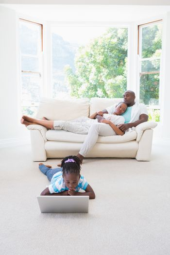 Pretty couple sitting on couch and their daughter using laptop