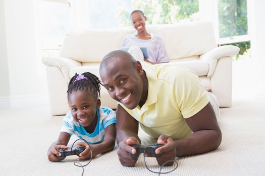 Portrait of a happy smiling father playing with her daughter at video games