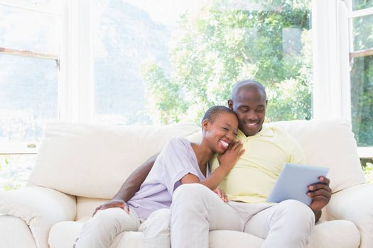 Happy smiling couple using laptop on couch