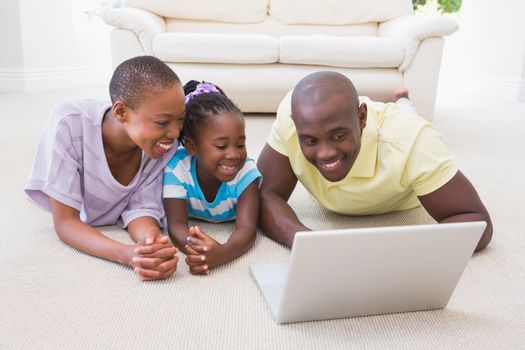 Happy smiling couple using laptop with their daughter