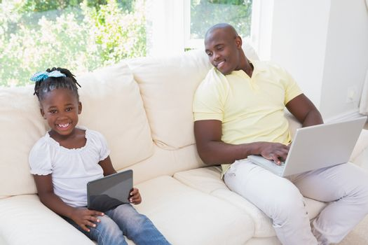 Happy smiling father using laptop and her daughter using tablet on couch