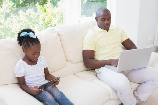Happy father using laptop and her daughter using tablet on couch