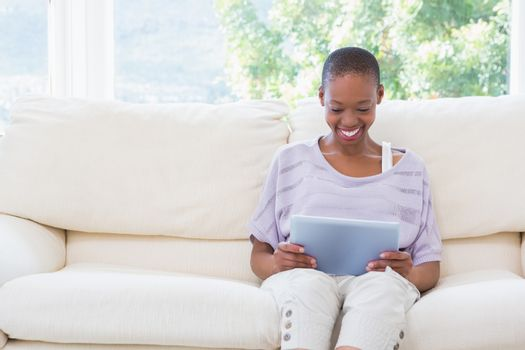 Happy smiling woman using digital tablet on couch