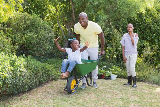 Happy smiling couple playing with wheelbarrow and their daughter