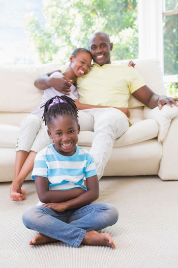 Portrait of a happy couple sitting on couh and their daughter sitting and looking at camera