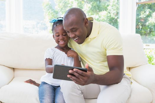 Happy smiling father using digital tablet with her daughter on couch