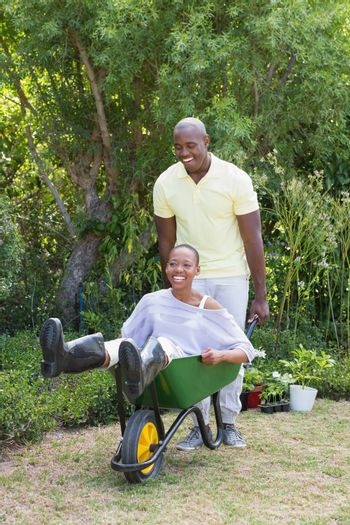 Happy smiling couple playing with wheelbarrow