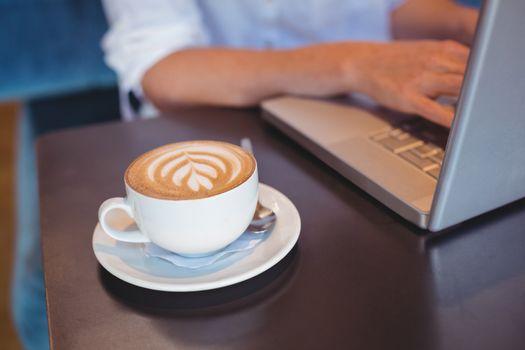 Pretty girl having coffee using laptop
