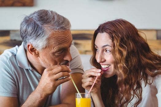 cute couple having glass of orange juice