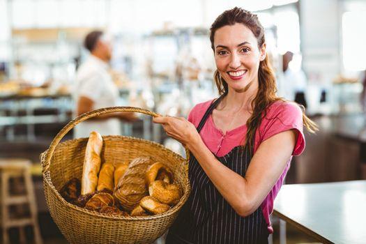 Pretty waitress carrying basket of bread