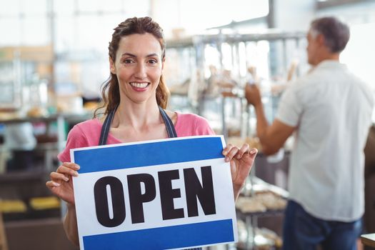 Pretty worker showing open sign