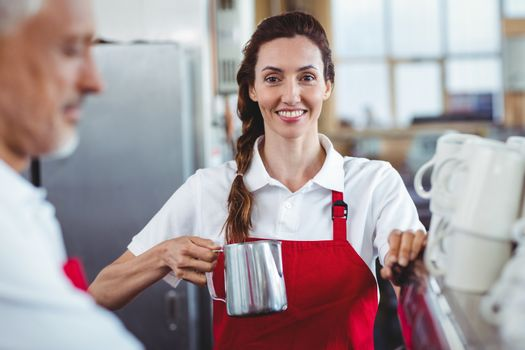 Pretty barista looking at camera and using the coffee machine