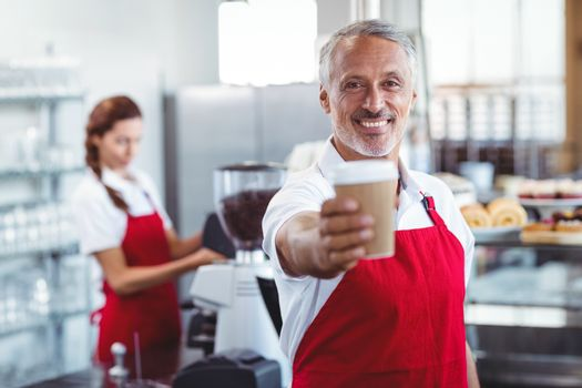 Happy barista giving take-away cup