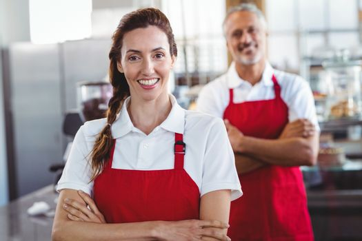 Two baristas smiling at the camera with arms crossed