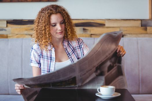 Pretty curly hair girl having cup of coffee and reading newspaper