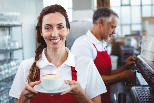 Smiling barista holding a cup of coffee with colleague behind