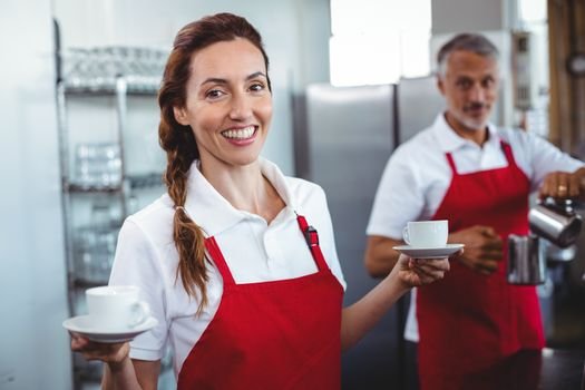 Pretty barista holding cups of coffee with colleague behind