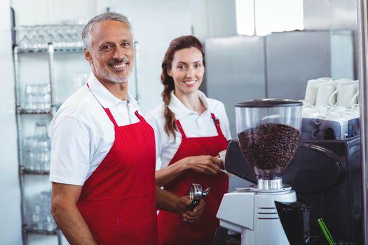 Two baristas smiling at the camera
