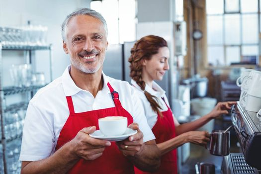 Happy barista smiling at camera and holding a cup of coffee