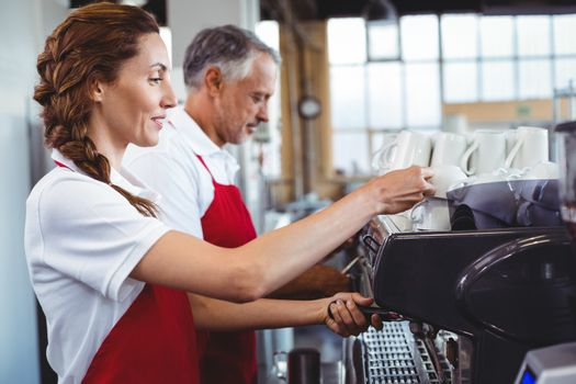 Pretty barista using the coffee machine with colleague behind