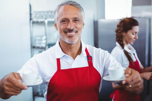 Smiling barista holding cups of coffee with colleague behind