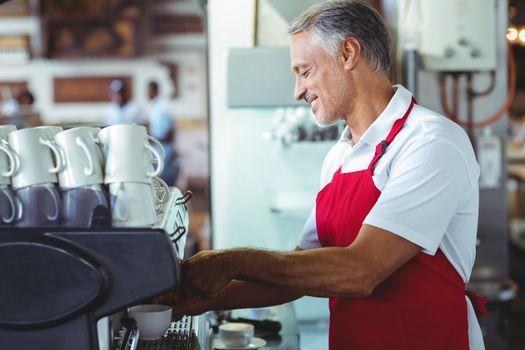 Happy barista using the coffee machine