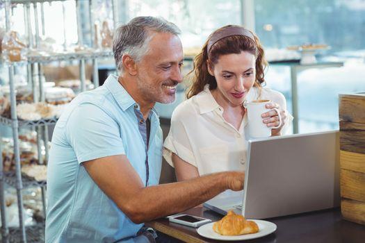 Happy couple pointing something on laptop