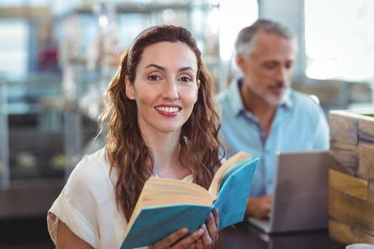 Pretty brunette looking at camera and holding book