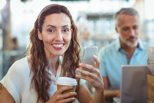 Pretty brunette looking at camera with smartphone and coffee in her hands