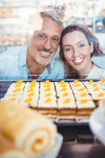 Happy couple looking at pastries through the glass