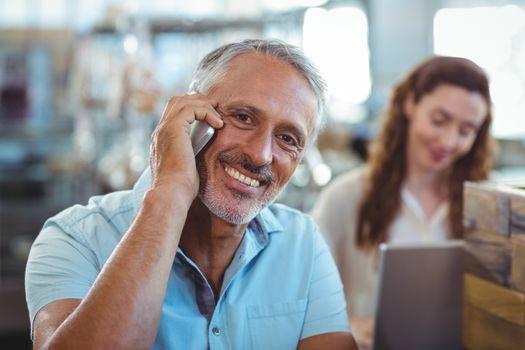 Happy man having phone call and smiling at camera