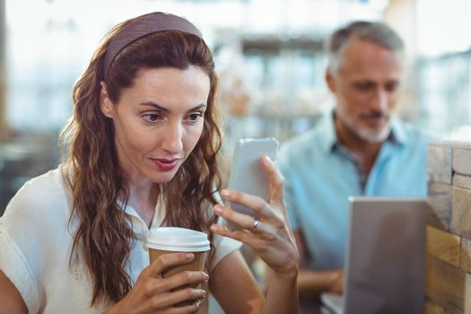 Pretty brunette using her smartphone with coffee in her hand