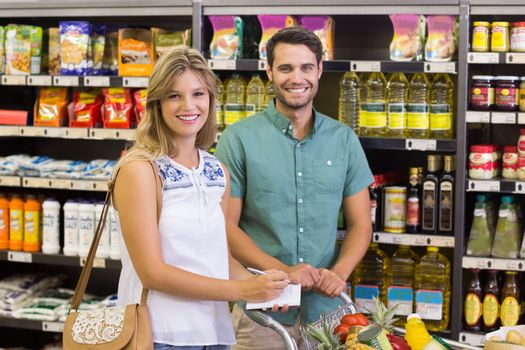 Portrait of smiling bright couple buying food products and uisng notebook