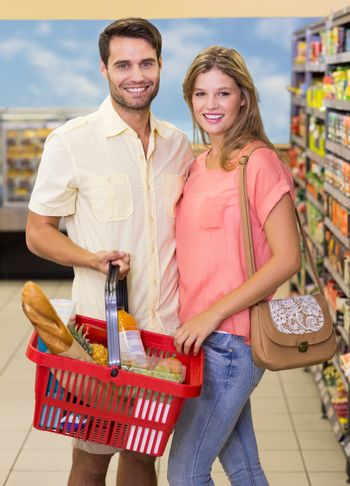 Portrait of smiling bright couple buying food products using shopping basket