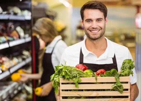 Portrait of a smiling staff man holding a box of fresh vegetables