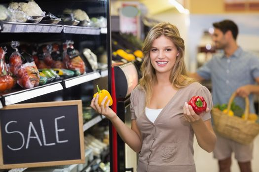 Portrait of a smiling pretty blonde woman buying vegetables