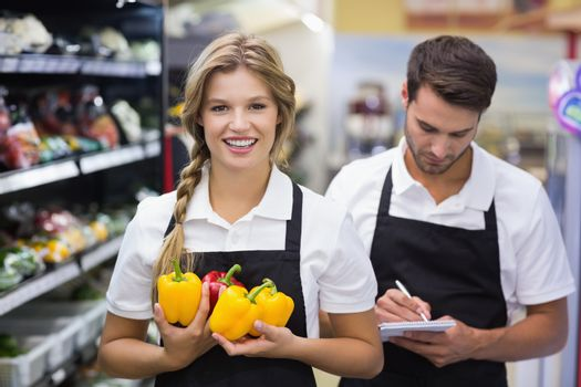 Portrait of smiling blonde woman having vegetables and writing on notepad