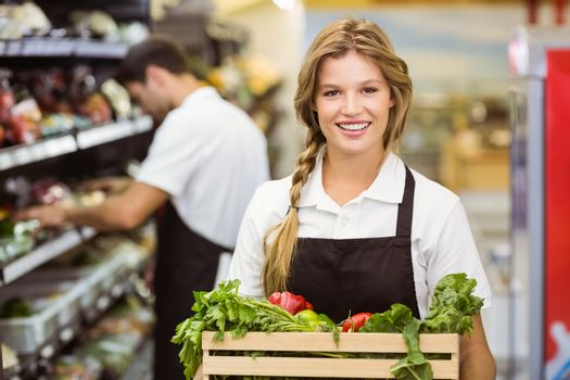 Portrait of smiling staff woman holding a box with fresh vegetables