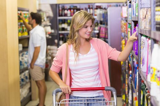 Smiling blonde woman taking a product on shelf