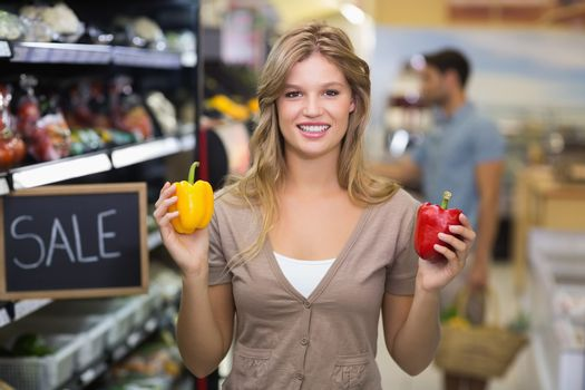 Portrait of a pretty smiling blonde woman buying vegetables