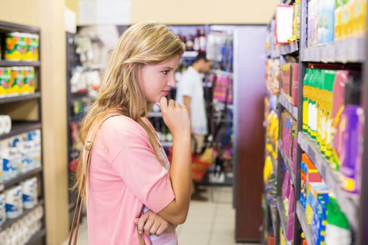 Pretty blonde woman looking at shelf and thinking