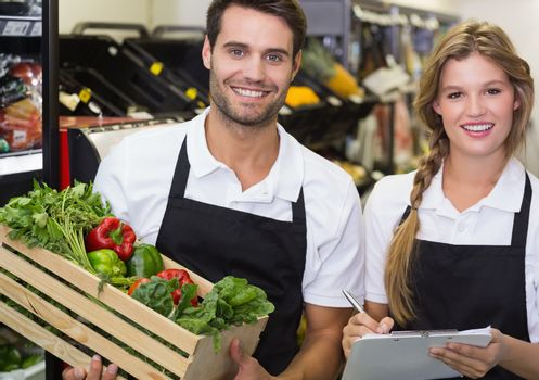 Portrait of two colleagues holding a box with fresh vegetables and writing on notepad