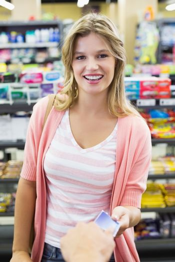 Portrait of a smiling woman paying at cash register paying with credit card