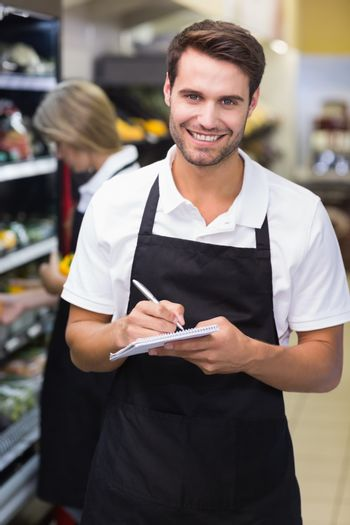 Portrait of smiling a staff man writing on notepad