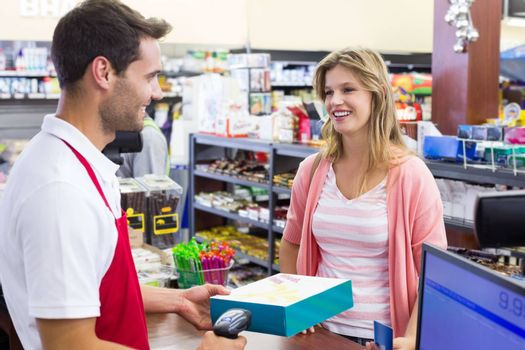 Smiling woman at cash register paying with credit card and scan a product