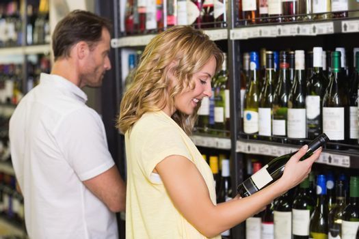 Smiling pretty woman looking at wine bottle