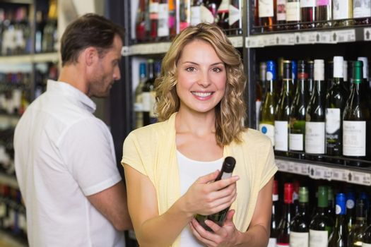 Portrait of smiling pretty blonde woman looking at wine bottle